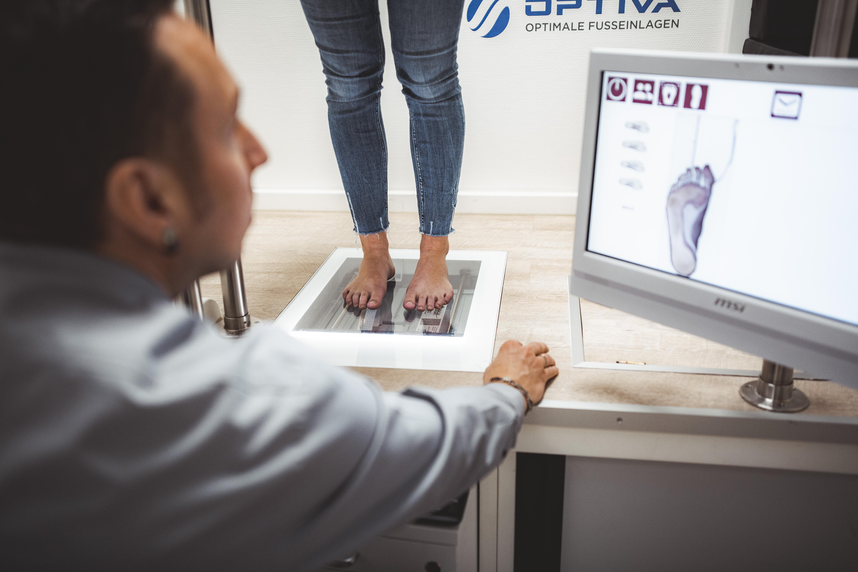 Mitarbeiter von Reha-OT und OPTIVA free vermessen einer Frau die Füße